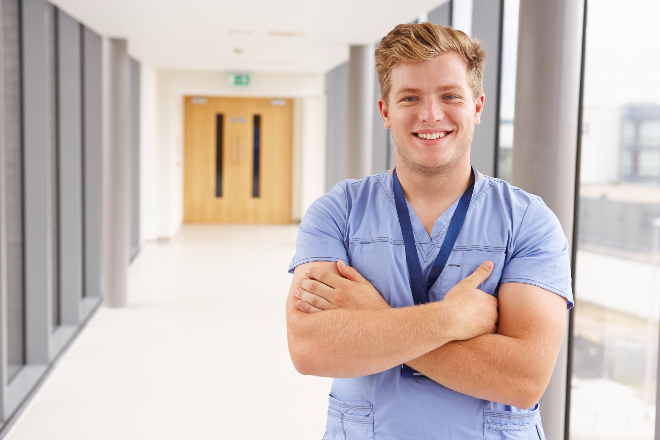 Portrait Of Male Nurse Standing In Hospital Corridor